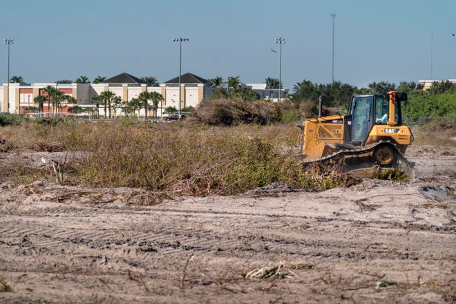 A bulldozer clears land for a park to be built south of Sunset Palms Elementary School in Boynton Beach. It will include athletic fields and two new lakes.