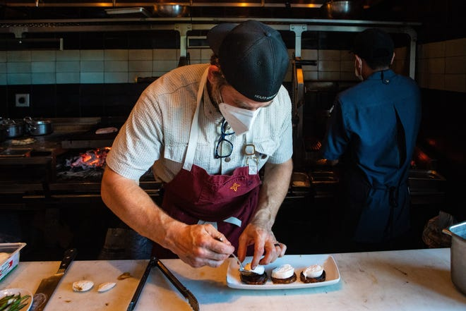 Clay Conley, chef and co-owner of Buccan Palm Beach, prepares a dish of Italian burrata over roasted sweet potato with a dusting of pistachio dukkah on Jan. 28.