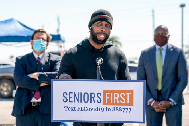 "Former Pahokee High and NFL football star Anquan Boldin appeared Wednesday with Gov. Ron DeSantis, left, and John Davis, secretary of the Florida Lottery, at a COVID-19 vaccination site in Pahokee. ""My job is to make sure the people out here are taken care of,"" he said."