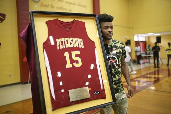 Frank Mason III stands with his framed Petersburg High School jersey during a jersey retirement ceremony in 2017.
