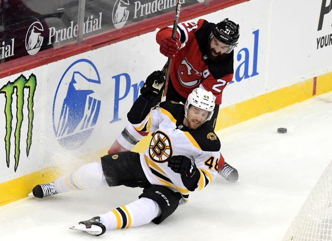 With two games scheduled for the weekend against the Buffalo Sabres canceled because of COVID concerns, Bruins defenseman Matt Grezelcyk, shown battling the Devils' Kyle Palmieri for the puck on Jan. 14, will have extra time to rehab a lower-body injury before next week.