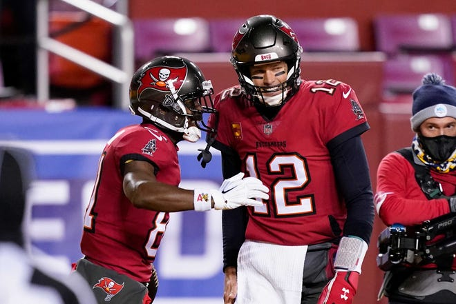Published Caption:  Buccaneers wide receiver Antonio Brown, left, celebrates his touchdown with quarterback Tom Brady during the first half of Saturday's NFC wildcard playoff game against the Washington Football Team.