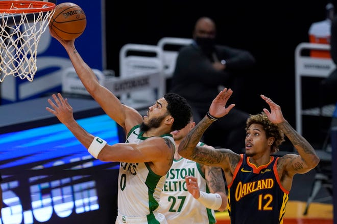 Boston Celtics forward Jayson Tatum, left, shoots next to Golden State Warriors guard Kelly Oubre Jr. (12) during the first half of an NBA basketball game in San Francisco, Tuesday, Feb. 2, 2021. (AP Photo/Jeff Chiu)