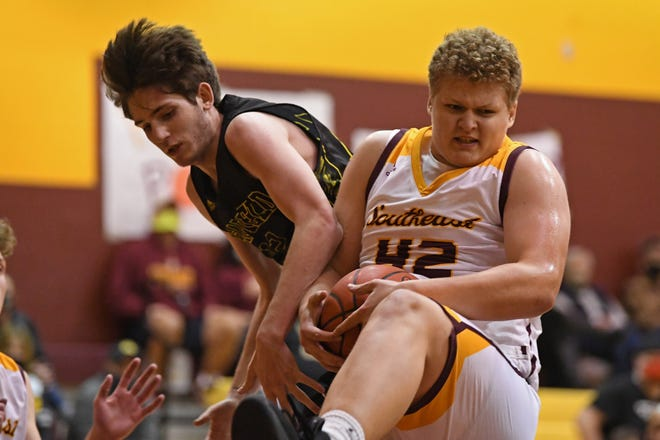 Southeast's Evan Riffle grabs a rebound away from Garfield's Kaidan Spade during the first half of their game, Tuesday at Southeast High School.