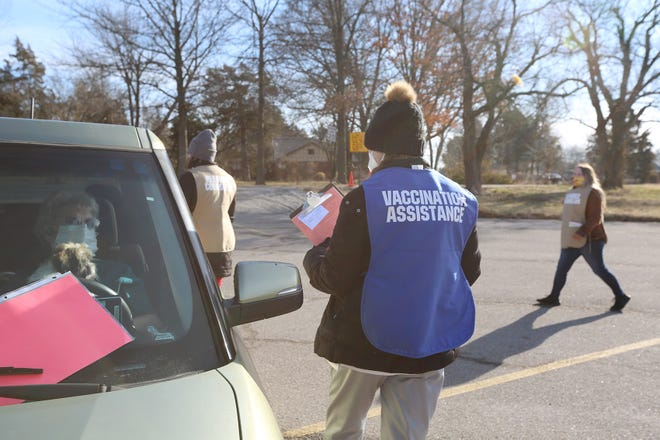 Volunteer meeting COVID-19 vaccine recipients at their car on Wednesday as the Crawford County Health Department held first vaccine drive-up clinic.
