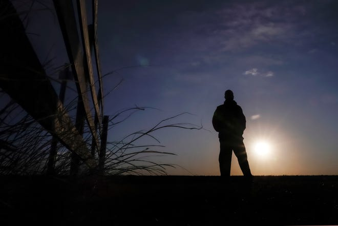 """Lateef Dowdell watches the sunrise from what remains of land once belonging to his uncle Gil Alexander, who was the last active Black farmer in the community of Nicodemus. Dowdell moved back to Nicodemus, a settlement founded by former slaves known as """"exodusters"""" in the 1870s, several years earlier to take over the farm after his uncle died, but soon after lost most of the land when the bank foreclosed."""