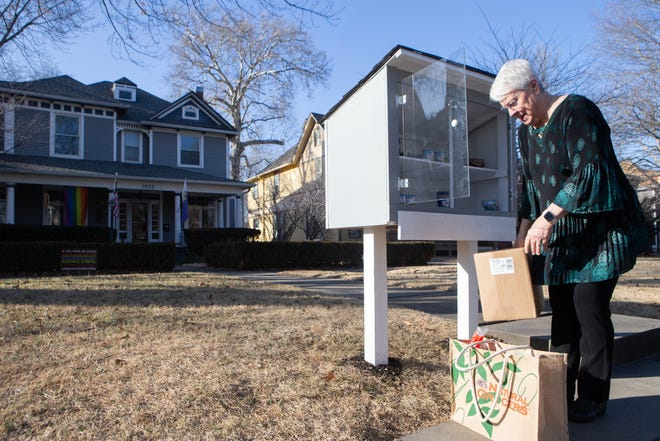 "Taking items from her '""bee's nest"" inside, Jeanine Russell fills up her blessing box outside her home Monday with food for those in need."