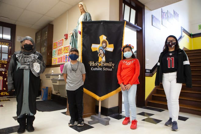 From left, Raegan Turvey, 11, Isaac Torres, 8, Gaby Garcia, 9, and Angelica Abrial, 12, dress like their favorite saint Tuesday morning inside Holy Family Catholic School, 1725 N.E. Seward Ave.
