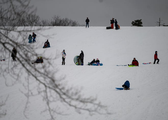 Families enjoy sledding at Green Hill Park on Tuesday.