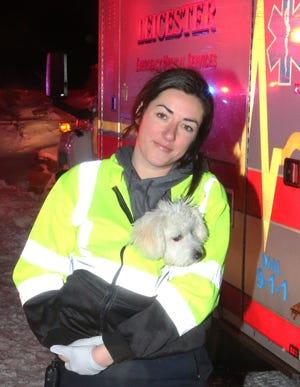 Leicester, Massachusetts, EMT Megan Cooney holds a dog on the plane that crashed in a field on Moose Hill Road Tuesday.