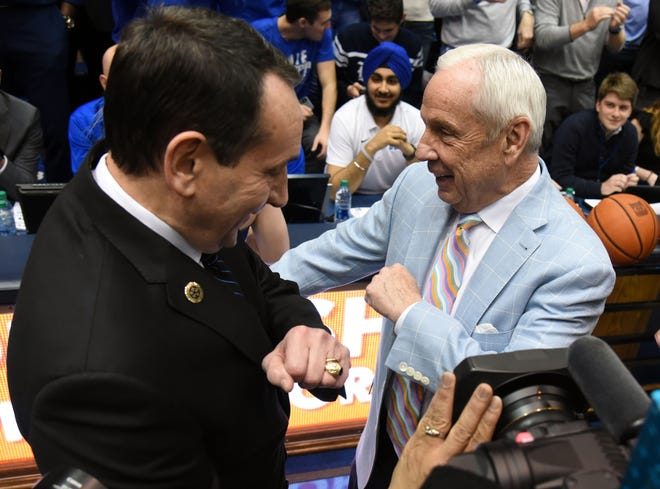 Mar 7, 2020; Durham, North Carolina, USA; Duke Blue Devils head coach Mike Krzyzewski (left) and North Carolina Tar Heels head coach Roy Williams exchange playful jabs prior to a game at Cameron Indoor Stadium. Mandatory Credit: Rob Kinnan-USA TODAY Sports