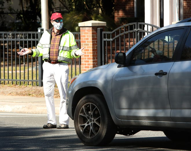 Gainesville Police Assistant Chief Terry Pierce gestures to a motorist as he walks across traffic on University Avenue during the start of operation Gator STEP, an increased enforcement program.
