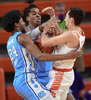 North Carolina's Kerwin Walton, front left, and Armando Bacot tangle with Clemson's Alex Hemenway, right, during Tuesday night's game at Littlejohn Coliseum.