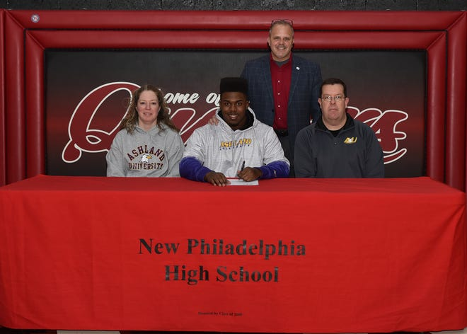 """New Philadelphia's Justin Rimer, son of Ben and Tracy Rimer, has signed his National Letter of Intent to continue his education and football career at Ashland University. Rimer, an All-Ohioan on the gridiron, was a three year starter and stand out on the offensive and defensive lines for the Quakers. He was a team captain and helped lead the Quakers to the """"Sweet 16"""" the past two seasons. He will be playing on the offensive line for the Eagles. Rimer sits between his mother and father with New Philadelphia head football coach Matt Dennison in the back."""