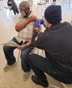 Erwin Jenkins of High Cliff Apartments gets his COVID-19 shot from Chuck Williams of Brewster Ambulance. Many elderly residents are frustrated with the registration process for the vaccine.