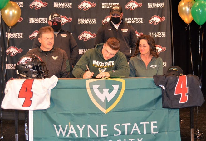 Bellevue's Nick Hayward signs to play football at Division 2 Wayne State University on Wednesday in front of friends and family at the Bellevue High School auditorium.