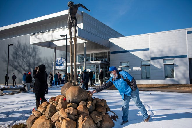 Mike Loader lays a rose to honor Russ Bortell on Wednesday, Feb. 3, 2021 at Kellogg Community College in Battle Creek, Mich. Longtime baseball coach at Kellogg Community College Russ Bortell, 63, passed away on Friday after a short fight with liver cancer.