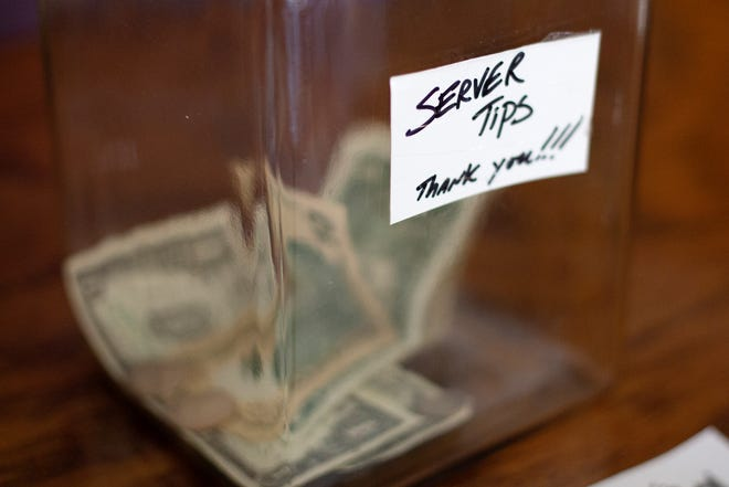 """A cash tip jar stands on the counter at Bellevue Bistro in Bellevue, Kentucky, on Wednesday, Feb. 3, 2021. The bistro was one of the most recent local restaurants to receive a $1,000-plus tip on an order in what's being called the """"Crosstown tip-off""""."""