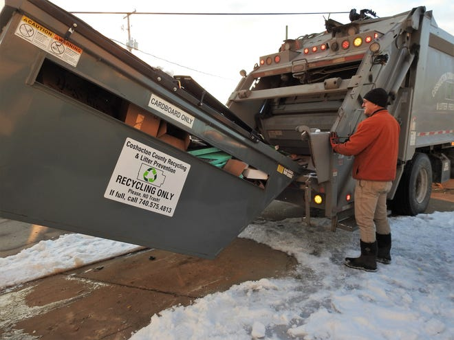 Tim Beck of Coshocton County Recycling and Litter Prevention empties a bin at the Coshocton County Maintenance Garage on County Road 621 into a packer truck for transport to a recycling center.