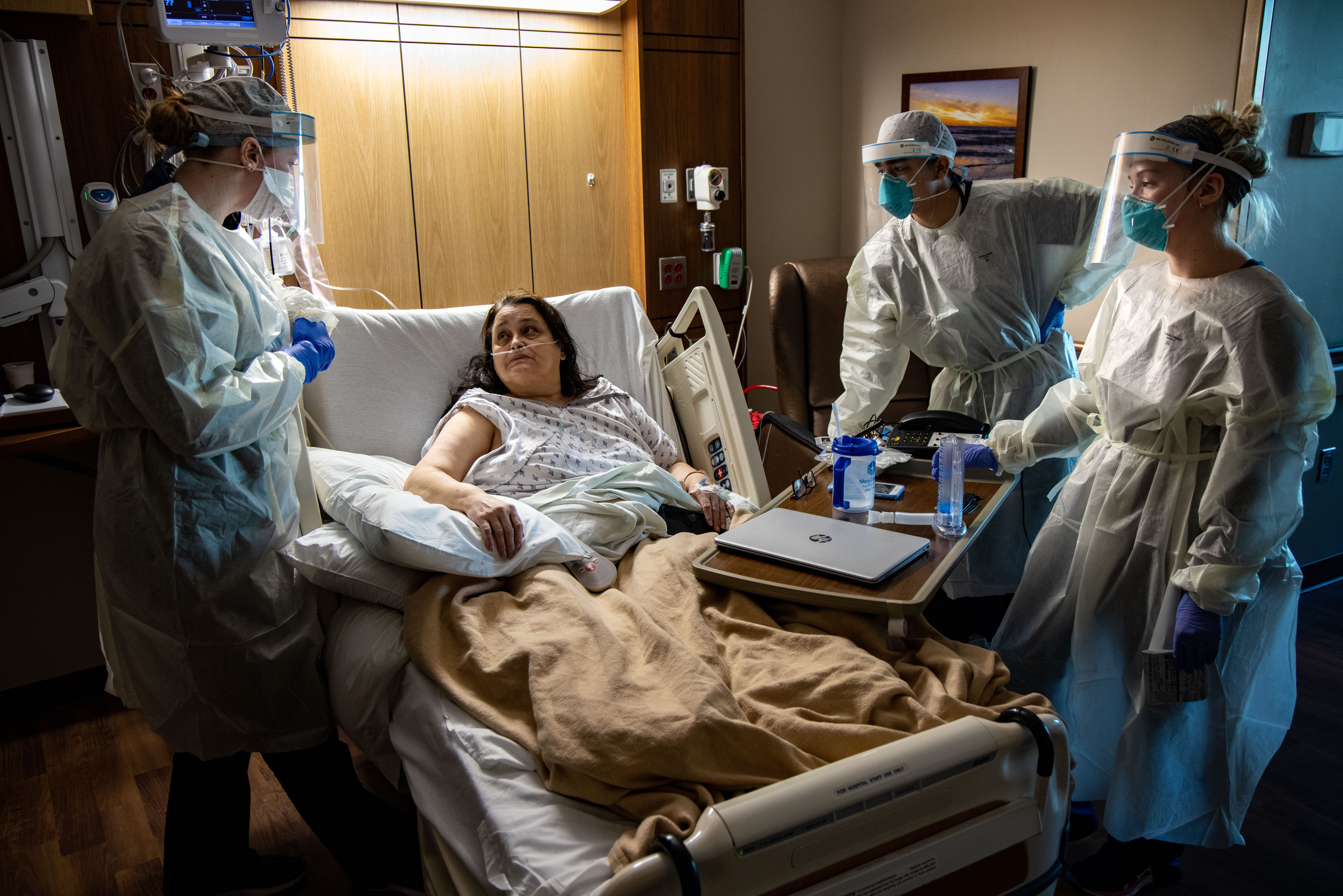 From left, nurses Connor Ramirez, Pedro Huerta and Lauren Carlson care for Mary Embrey as she recovers from COVID-19 at Mary Greeley on Dec. 9.