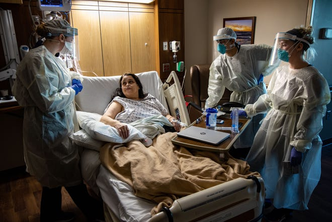 From left, nurses Connor Ramirez, Pedro Huerta and Lauren Carlson care for a patient at Mary Greeley Medical Center in Ames on Dec. 9, 2020.