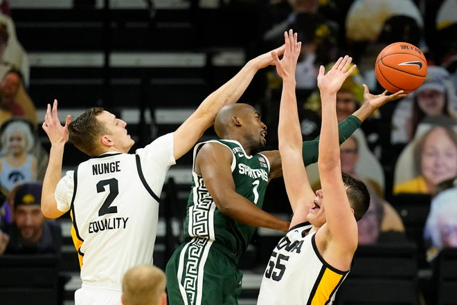 Michigan State guard Joshua Langford (1) drives to the basket between Iowa forward Jack Nunge (2) and center Luka Garza, right, during the second half of an NCAA college basketball game, Tuesday, Feb. 2, 2021, in Iowa City, Iowa. Iowa won 84-78.