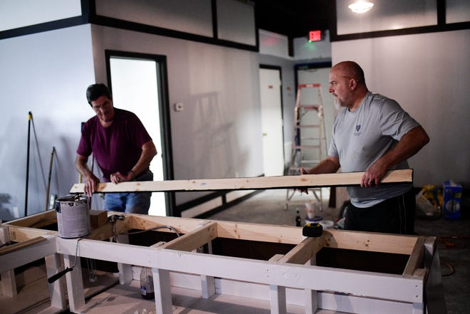 Jason Able and his father-in-law, Ralph Swallows, work on building the counter at the upcoming South Knox Nutrition on Sevier Ave. in Knoxville, Tenn. on Saturday, Feb. 30, 2021. The smoothie and tea shop plans to open near the end of the month.