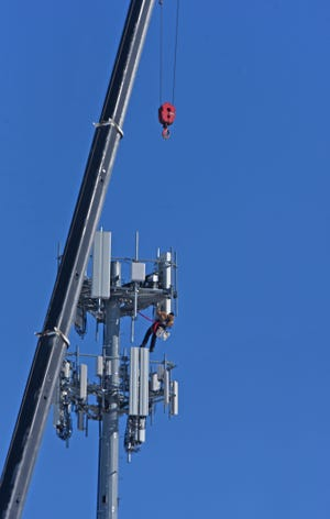 A worker hangs high in the chilly air Wednesday afternoon near the Trimble Road and U.S. 30 exchange while making updates to a cellular tower.
