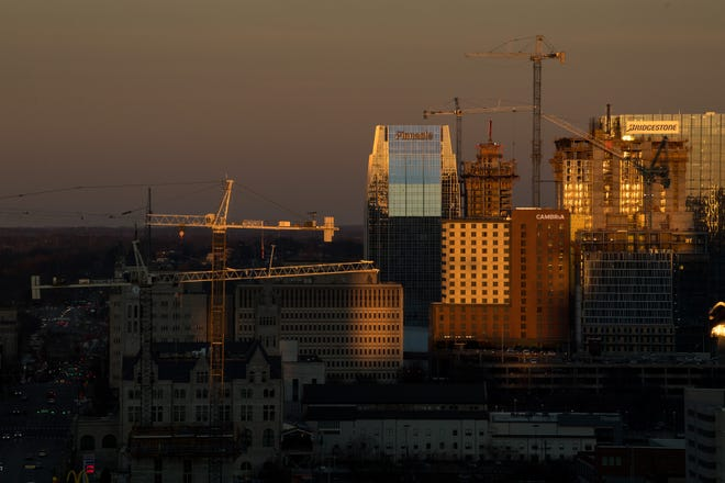 Construction cranes are seen on the skyline as the sun sets over downtown Nashville, Tenn., Wednesday, Feb. 3, 2021.