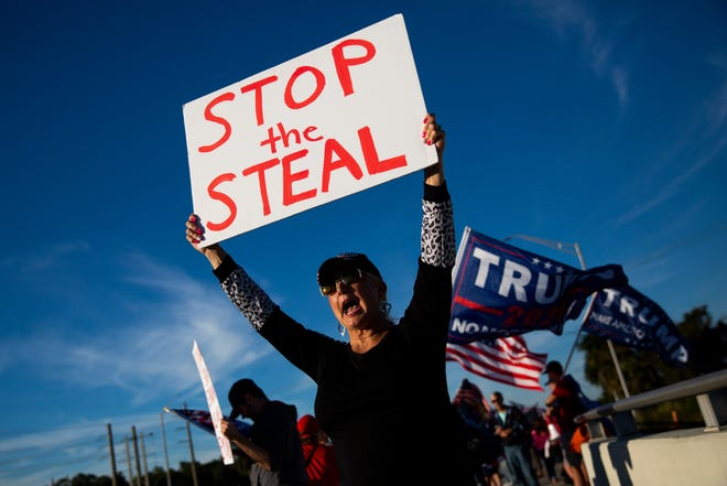 """Diane """"Feisty"""" Feist holds up a sign that says """"stop the steal"""" during a pro-Trump protest outside Oakes Farms Seed to Table in North Naples on Wednesday, January 6, 2021."""