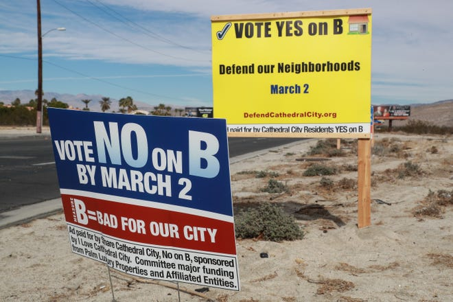 Opposing signs for and against Measure B sit on Date Palm Drive in Cathedral City, Calif on Wednesday, February 3, 2021. The ballot initiative will allow voters to decide on the future of short-term rentals in the city during a March 2 special election.