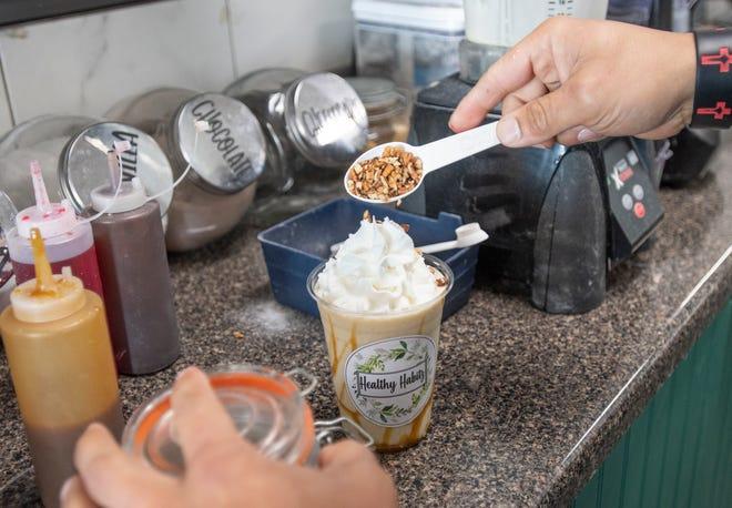 Owner Matt Mercado tops off a Butter Pecan Ice Cream vanilla protein shake at Healthy Habitz on North Davis Highway in Pensacola on Tuesday, Feb. 2, 2021.