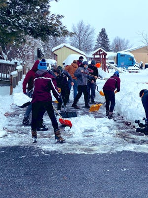 Shippensburg football players shovel out a local driveway as part of a team-wide activity on Tuesday afternoon.