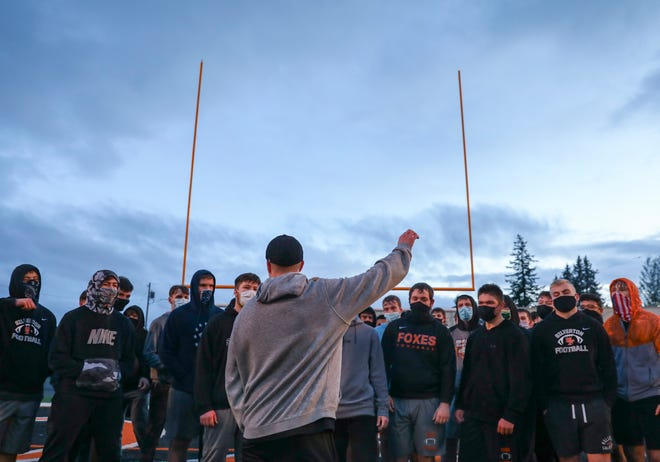 Silverton High School football head coach Josh Craig huddles with the team at the end of practice in Silverton. The 5A Silver Foxes play against 6A West Salem on Saturday.