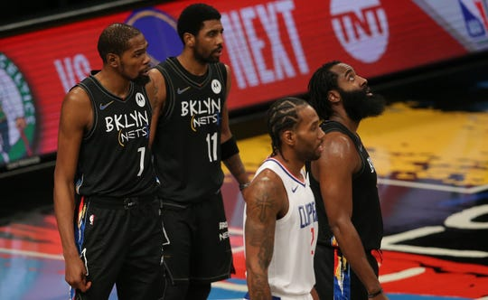 The Nets' Kevin Durant (7), Kyrie Irving (11) and James Harden (13), along with the Clippers' Kawhi Leonard, look on during a review in Brooklyn's 124-120 win Tuesday night.