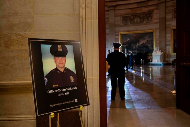 A photo of the fallen Capitol Police officer Brian Sicknick is seen as people wait for his remainsto arrive to lay in honor in the Rotunda of the US Capitol on Feb. 2, 2021, in Washington, DC.