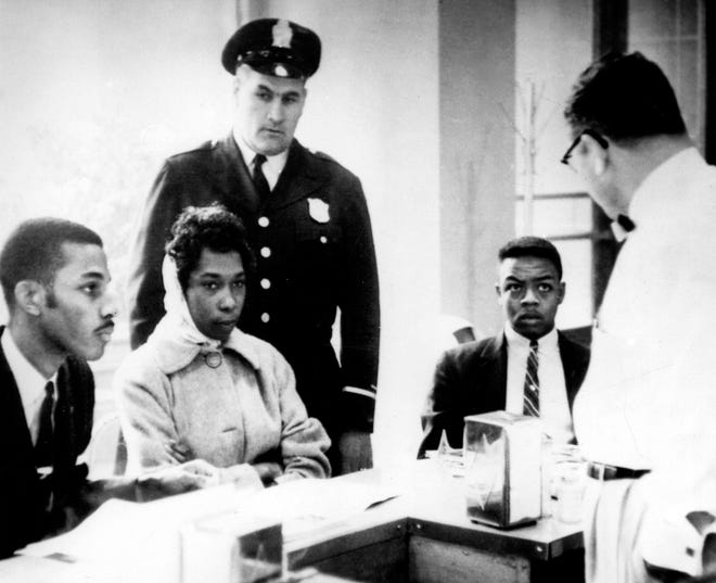 Victor Cobb, the manager of a dining room in Atlanta's Trailways Bus Terminal, asks African Americans to leave his lunch counter on March 16, 1960. The demonstrators stared at him in silence, refused to leave and were arrested by the officer.