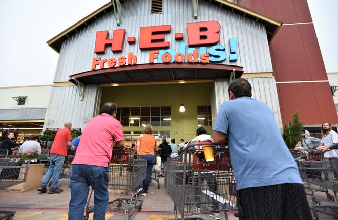 Shoppers line up at Bastrop H-E-B before an 8 a.m. opening on Sunday. The store compressed its hours of operation to give staff additional time to stock products which are selling out quickly amid the novel coronavirus pandemic.