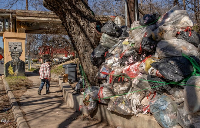 Glenn Cude, who said he has been homeless for 20 years, walks past a pile of trash Thursday at a homeless camp on Barton Springs Road near South Lamar Boulevard.