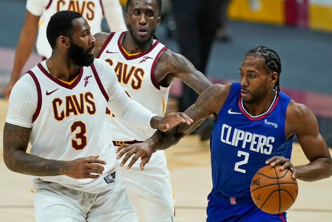 Los Angeles Clippers' Kawhi Leonard (2) drives against Cleveland Cavaliers' Andre Drummond (3) during the second half of an NBA basketball game Wednesday, Feb. 3, 2021, in Cleveland. (AP Photo/Tony Dejak)