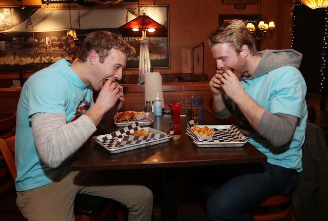 Jonathon Giaquinto, left, and John Iacano eat their hamburger rewards Tuesday after trying all 50 types of hamburgers on the menu at Menches Brothers Restaurant & Pub in Green.