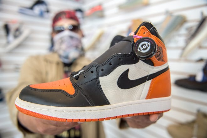"""Owner Maurice Tolliver holds an Air Jordan 1 """"Shattered Backboard"""" shoe at his newly opened The Retro Store 803 in North Augusta. The collectible shoe costs around $2,000."""