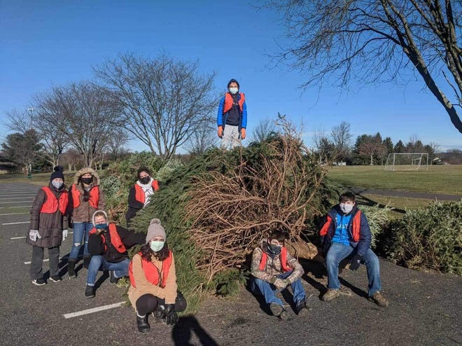 Student members of Souderton Area High School's organizations SAVE and National Honor Society held a recycling event in January and collected discarded Christmas trees from the community. Branches will be made into mulch for use in the township's flower beds and nature trails. [PHOTO PROVIDED]