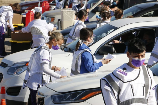 Health care workers who staffed the COVID drive-through vaccination clinic Wednesday at Gordon Wood Stadium prepare to give vaccinations as vehicles occupy the six lanes marked off in the stadium parking area.