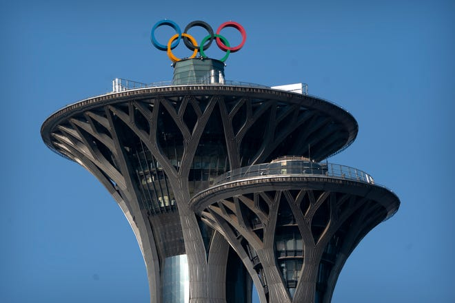 The Olympic rings are visible atop the Olympic Tower in Beijing, Tuesday, Feb. 2, 2021. The 2022 Beijing Winter Olympics will open a year from now.