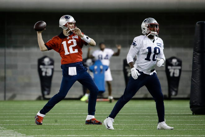 New England Patriots quarterback Tom Brady (12) throws a pass as Matthew Slater (18) warms up during a January 2019 practice ahead of Super Bowl LIII against the Los Angeles Rams in Atlanta.