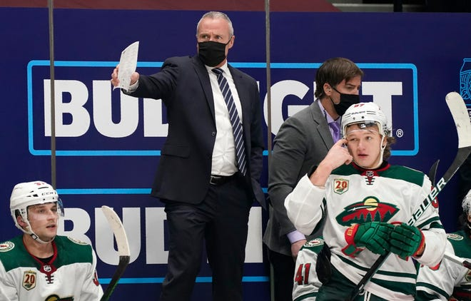 Minnesota Wild coach Dean Evason, back, directs the team during Tuesday's game against the Colorado Avalanche in Denver.