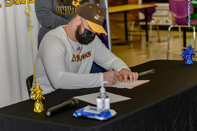 Hickman's Adison Barnett-Hill signs his national letter of intent to play football at Quincy University on Wednesday at Hickman High School.