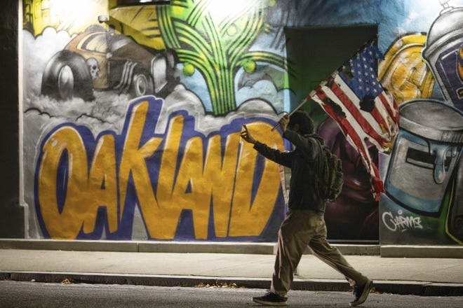A man walks in front of a mural in Oakland, Calif., in July during a protest against police violence and racial injustice. As in Columbus and in many other large cities, Oakland had a terrible year in 2020 when it came to homicidal violence. But Oakland's success in reducing violent crime during the 2010s provides a model for Columbus.