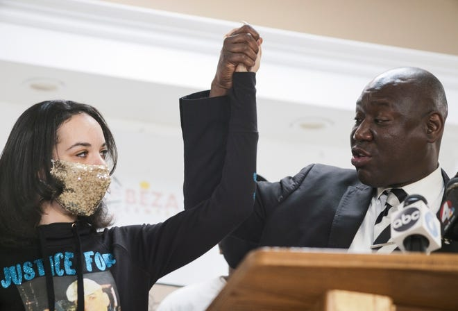 Karissa Hill, left, daughter of Andre Hill, and attorney Ben Crump, right, raise their hands as they speak during a news conference following the indictment of former Columbus police officer Adam Coy Thursday at the Beze Community Center in Columbus. Coy was indicted on four charges in the December 2020 shooting death of Andre Hill, a Black man. Coy was charged with one count of murder, one count of felonious assault and two counts of dereliction of duty, one of which was for failure to render aid to Hill after he was shot.